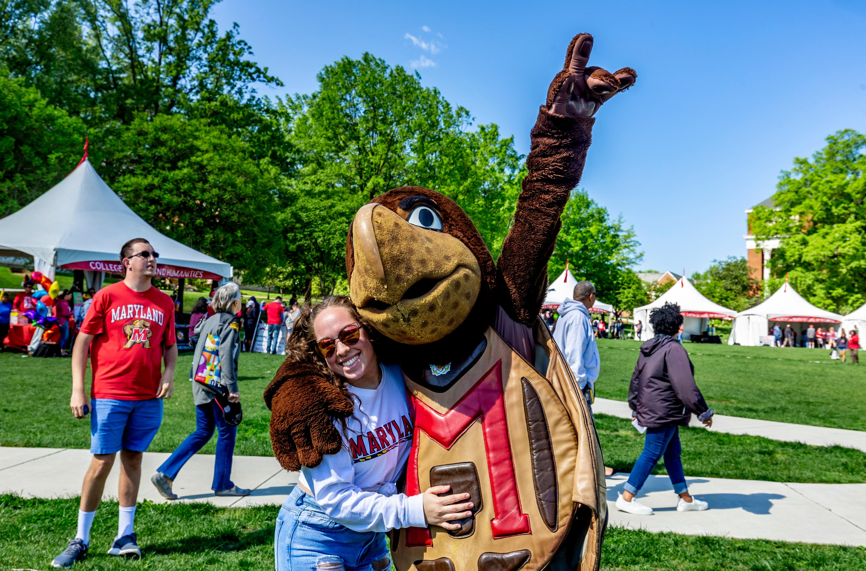 Testudo and woman in Maryland sweatshirt on Maryland Day 2019. Photo by Stephanie S. Cordle.